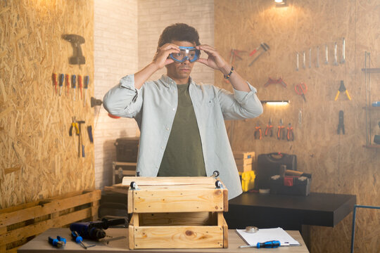 Portrait of a carpenter putting on safety goggles