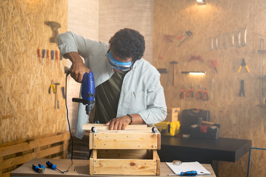 Carpenter with safety goggles using drill in workshop