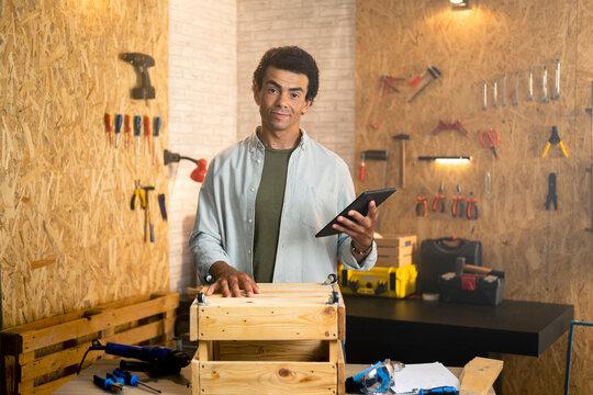 Portrait of a carpenter in workshop holding tablet