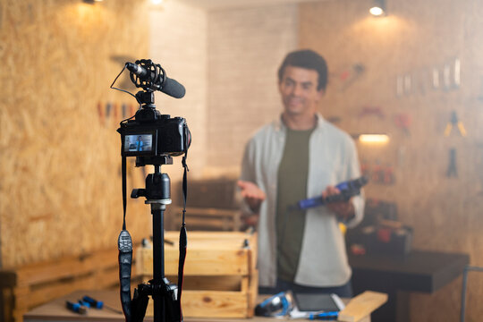 DIY carpenter filming a blog about drill with focus on camera and a carpenter blurred in the back