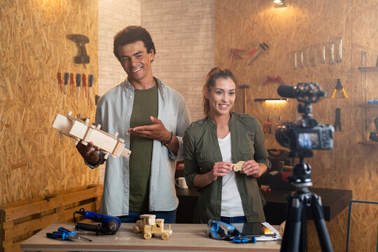 Two people in a carpentry workshop being filmed with a camera for a blog