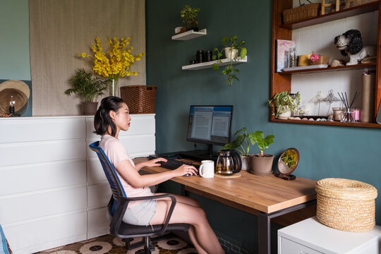 Asian woman reading document on computer and working at home