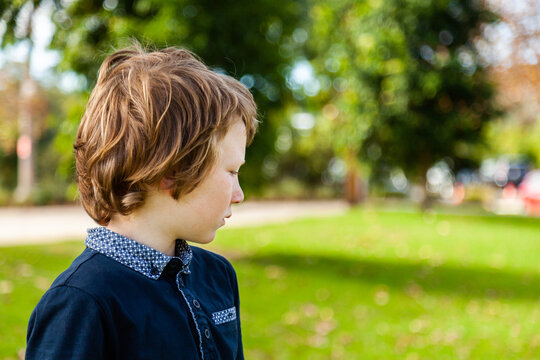 profile of unsure young autistic boy looking to the side at a park outside