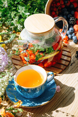 Fototapeta natural aromatic fruit tea in a transparent teapot and in a cup among berries and flowers. warming aromatic tea with a deep aroma of berries and wildflowers. obraz