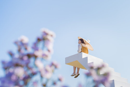asian woman relax and hold umbella on white stair in flower garden on springtime vacation