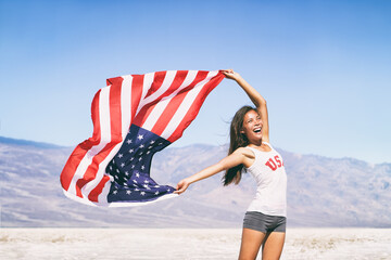 Fototapeta USA flag happy American Asian sports athlete woman waving after game winning cheering at outdoor landscape summer nature. obraz