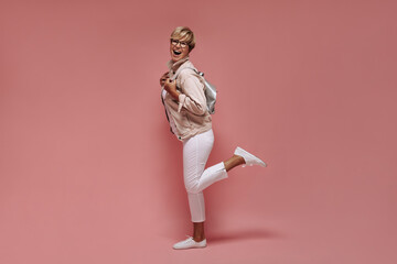 Fototapeta Exciting woman with blonde hair and cool glasses in white trousers and stylish jacket laughing on isolated pink background.. obraz