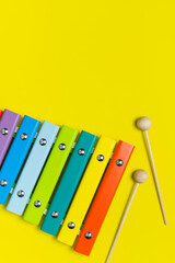 Multicolored wooden xylophone and shock sticks on bright yellow background flat lay top view copy...