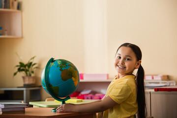 Fototapeta joyful asian girl smiling at camera near globe in montessori school obraz