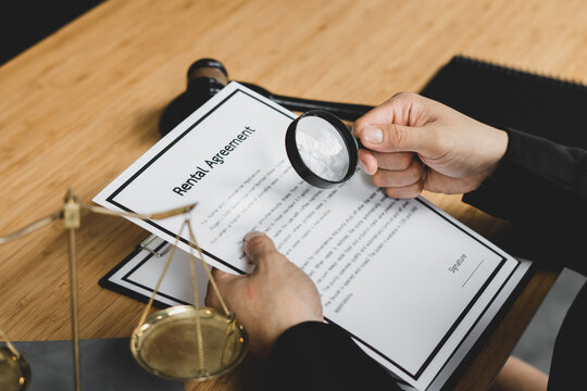 Midsection Of Lawyer Examining Paper Through Magnifying Glass By Gavel On Desk