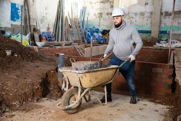 Young worker carrying bucket with cement mortar on small cart in building under construction