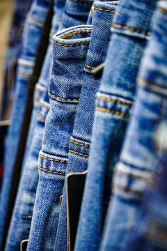 a lot of blue jeans hang in a row on hangers in a store, clothing sale, wardrobe, vertical wallpaper for stories