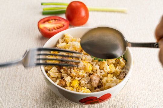 Man hand using metal spoon and fork scoop delicious thai style homemade pork and egg fried rice.