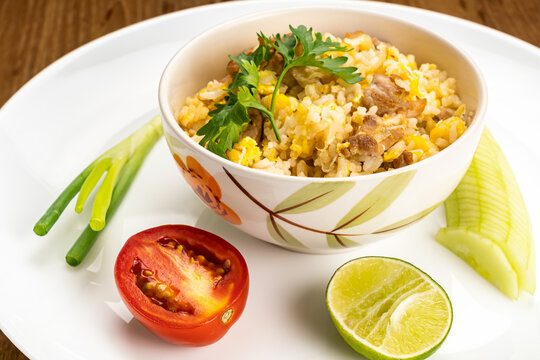 View of thai style delicious homemade fried rice with pork, egg, garlic and pepper in ceramic bowl.