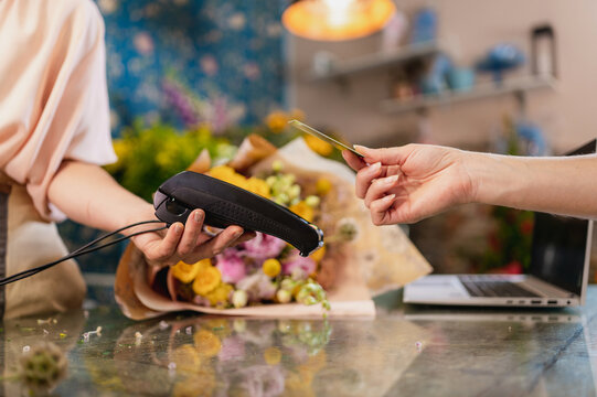 Crop client paying with plastic card on POS terminal in flower shop