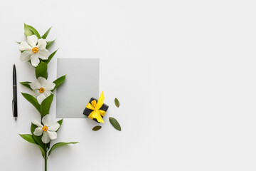 Beautiful daffodils, gift box and blank card on white background