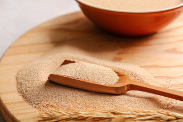 Scoop with active dry yeast on wooden board, closeup