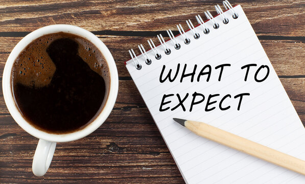 WHAT TO EXPECT text on notebook with coffee on the wooden background