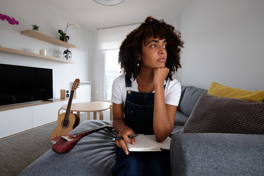 Black musician composing music at home