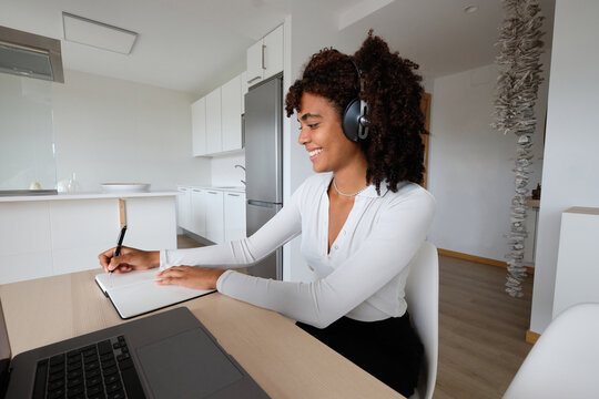 Black woman in headphones taking notes and working from home