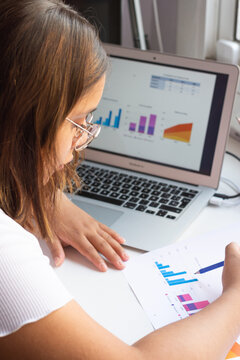 vertical image of a beautiful young Latin American businesswoman reviewing the graphs to know where to invest in the office.
