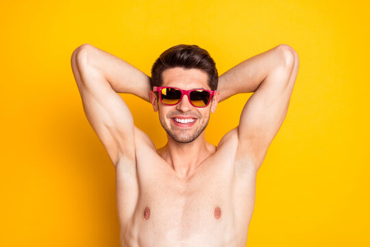 Photo of attractive sweet young man naked torso dark eyewear arms behind head smiling isolated yellow color background