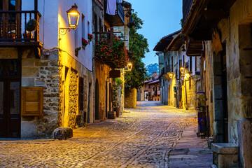 Smalle steeg van oude stenen stad met geplaveide straatjes & 39 s avonds verlicht.
