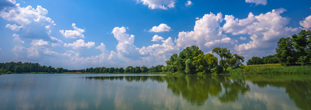 Low angle shot of the beautiful sky captured from a lake in a field