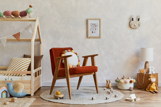 Stylish composition of cozy scandinavian child's room interior with wooden bed, red armchair, plush and wooden toys and textile decorations. Creative wall, carpet on the floor. Copy space. Template.