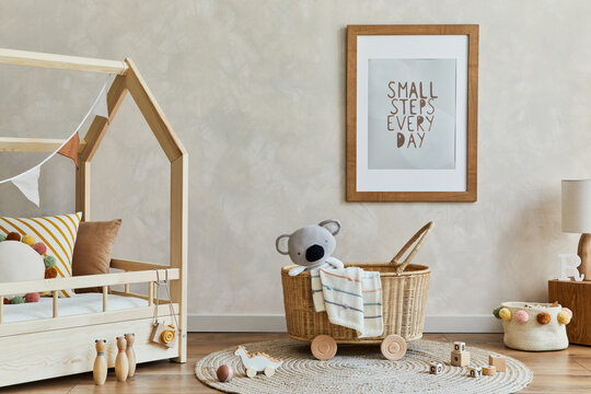 Stylish composition of cozy scandi child's room interior with mock up poster frame, bed, rattan basket, plush and wooden toys and decorations. Creative wall, carpet on the floor. Copy space.