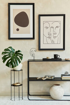 Creative composition of stylish modern living room interior with two mock up poster frames, black geometric commode, leaf in vase and personal accessories. Neutral corols. Template.