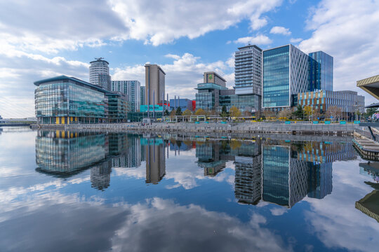 View of MediaCity and clouds reflecting in water in Salford Quays, Manchester, England