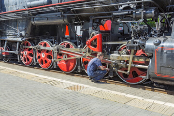 Worker inspects a black retro steam locomotive on the railway platform of the Rizhsky station. Moscow, Russia