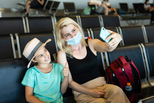 Mother and daughter tourist wearing protective hygiene mask on faces sitting in airport terminal. Idea for safety of new normal traveler and social distancing.