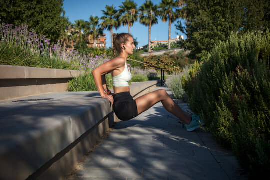 Side view of an athletic girl doing triceps down dips, in a park and natural environment.
