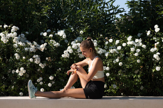 Sporty caucasic woman sitting on a bench with a flower background looking at her smartwatch