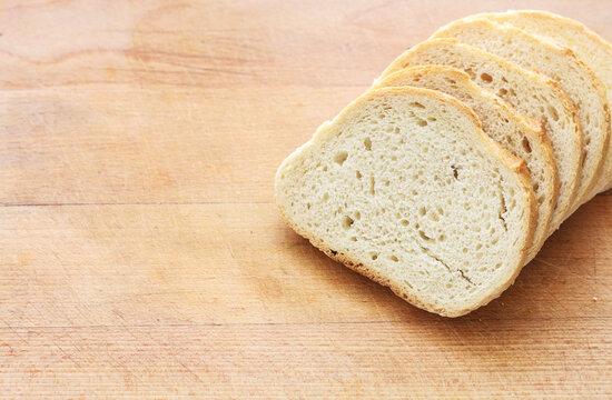 Sliced bread on wooden cutting board.