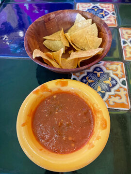 Mexican Salsa and chips in seperate bowls on a tiled table in a Mexican restaurant in Douglas AZ