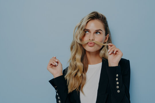 Funny joyful blonde woman having fun while posing against blue studio wall, playing with strand of hair