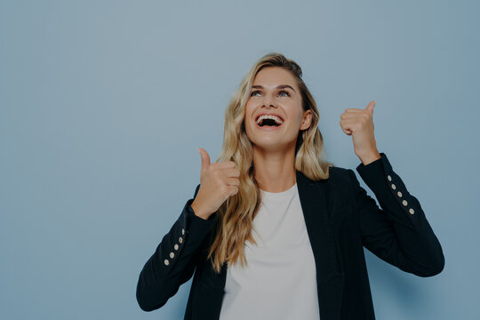 Bright laughing young woman showing thumbs up gesture with both hands