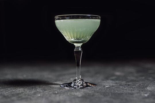 Last Word green chartreuse cocktail in elegant stemware against dark background