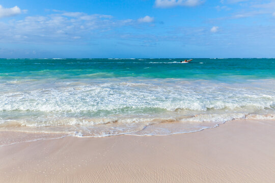 Small motorboat goes along the Bavaro beach on a sunny day