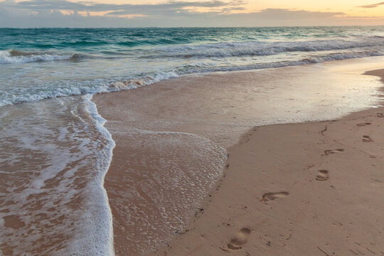 Colorful sunrise at the beach. Landscape with bare footprints