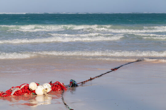 Red white floats on a rope lay over wet sandy coast