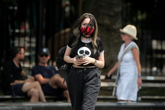 A woman wears a mask, as cases of the infectious Delta variant of COVID-19 continue to rise, in Washington Square Park in New York