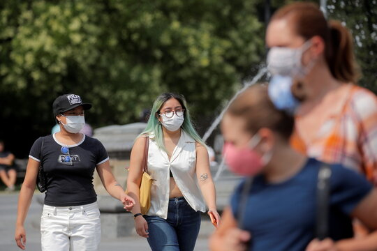 People wear masks, as cases of the infectious Delta variant of COVID-19 continue to rise, in Washington Square Park in New York