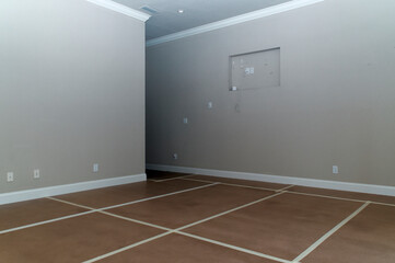 Fototapeta A big empty neutral colored room room with tape on the floor forming a grid and numerous outlets obraz