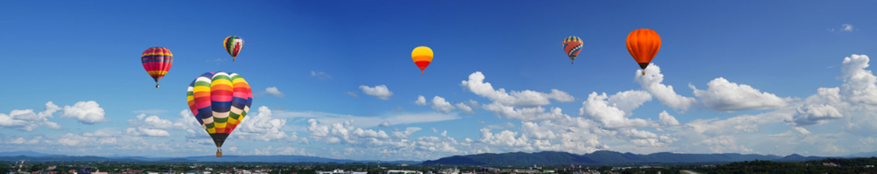 panorama of color hot air balloons in blue sky over the city background.