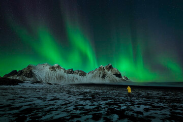 Beautiful scenery of Northern lights on night sky over Vesturhorn mountains with black sand beach and snow in Southeast Iceland during winter time. One of the most popular tourist spots in Iceland.