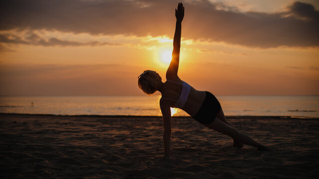 Woman doing yoga stretches on the beach with a hot orange sun shining behind her at sunset
